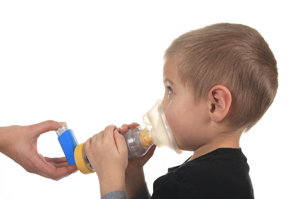 Child being helped using a spacer for asthma medication