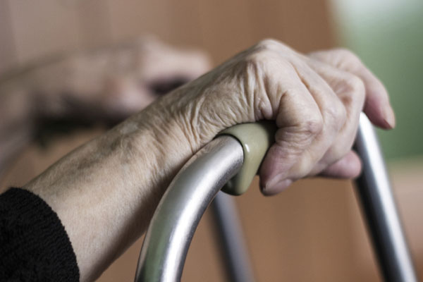 Close up of old womens hands resting on the top of her walking frame