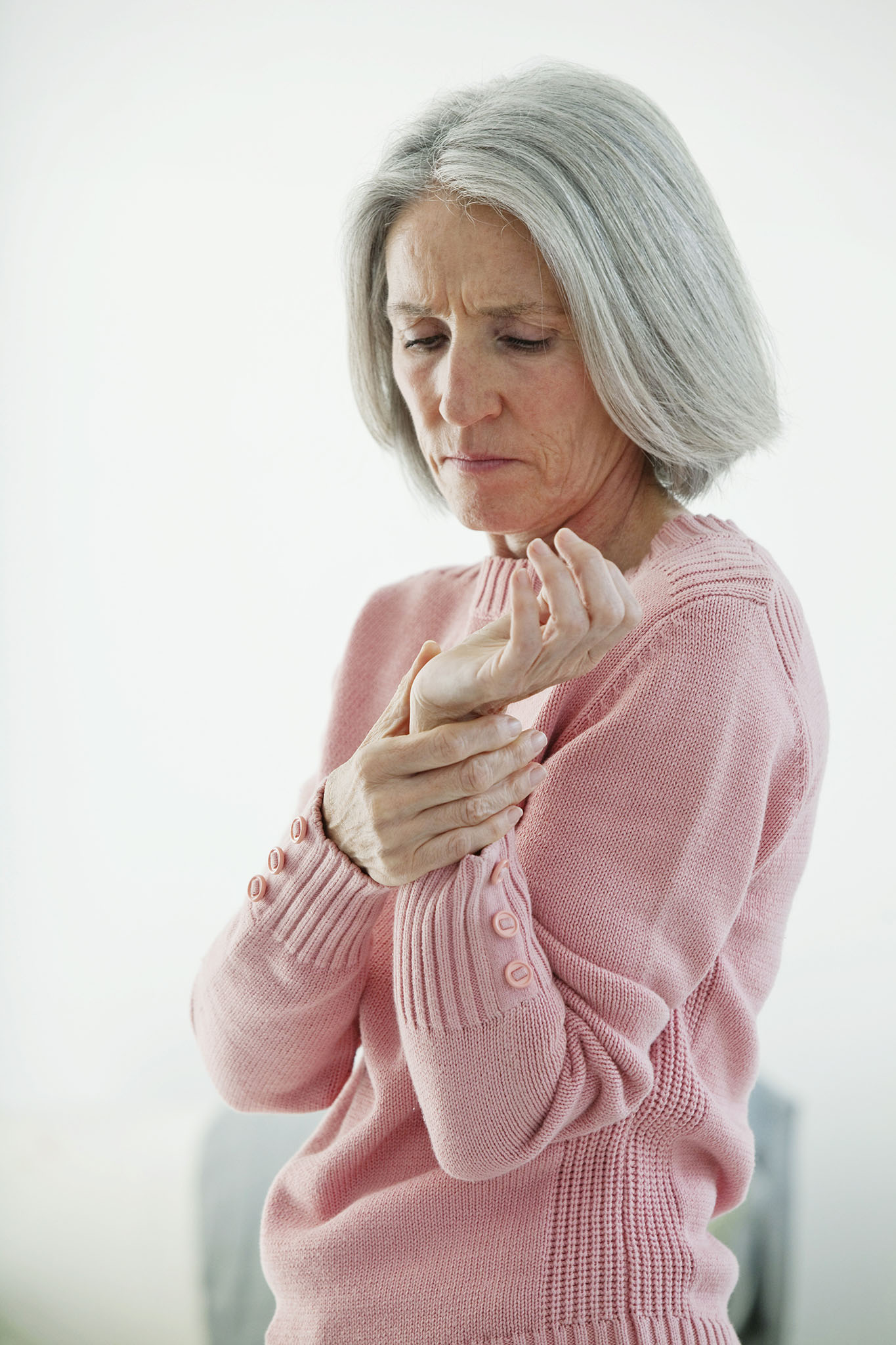 Elderly women examining her sore wrist