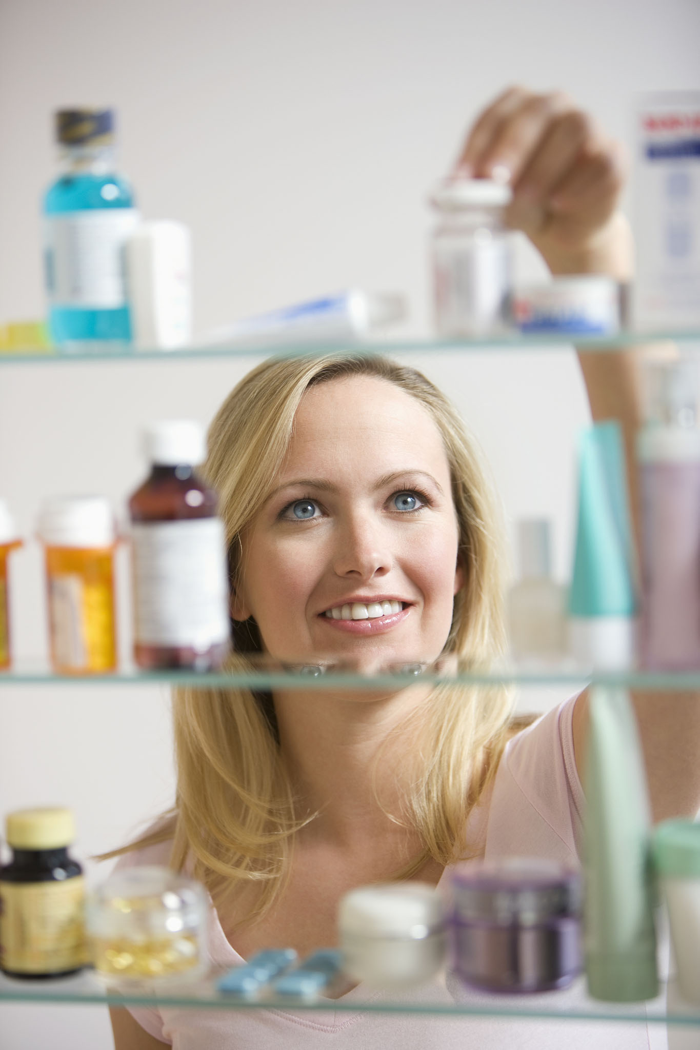 Smiling woman placing medicine on shelves