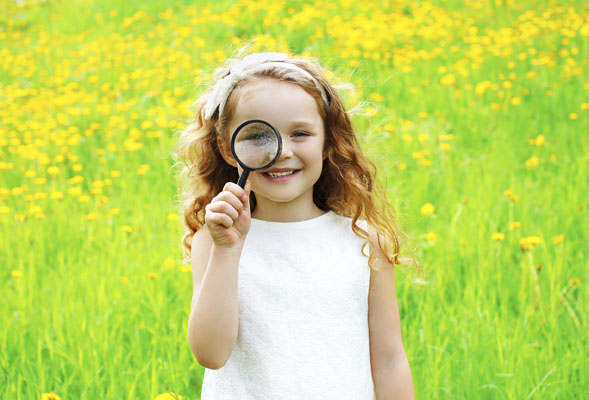 Smiling girl standing in a green field looking through a magnifying glass