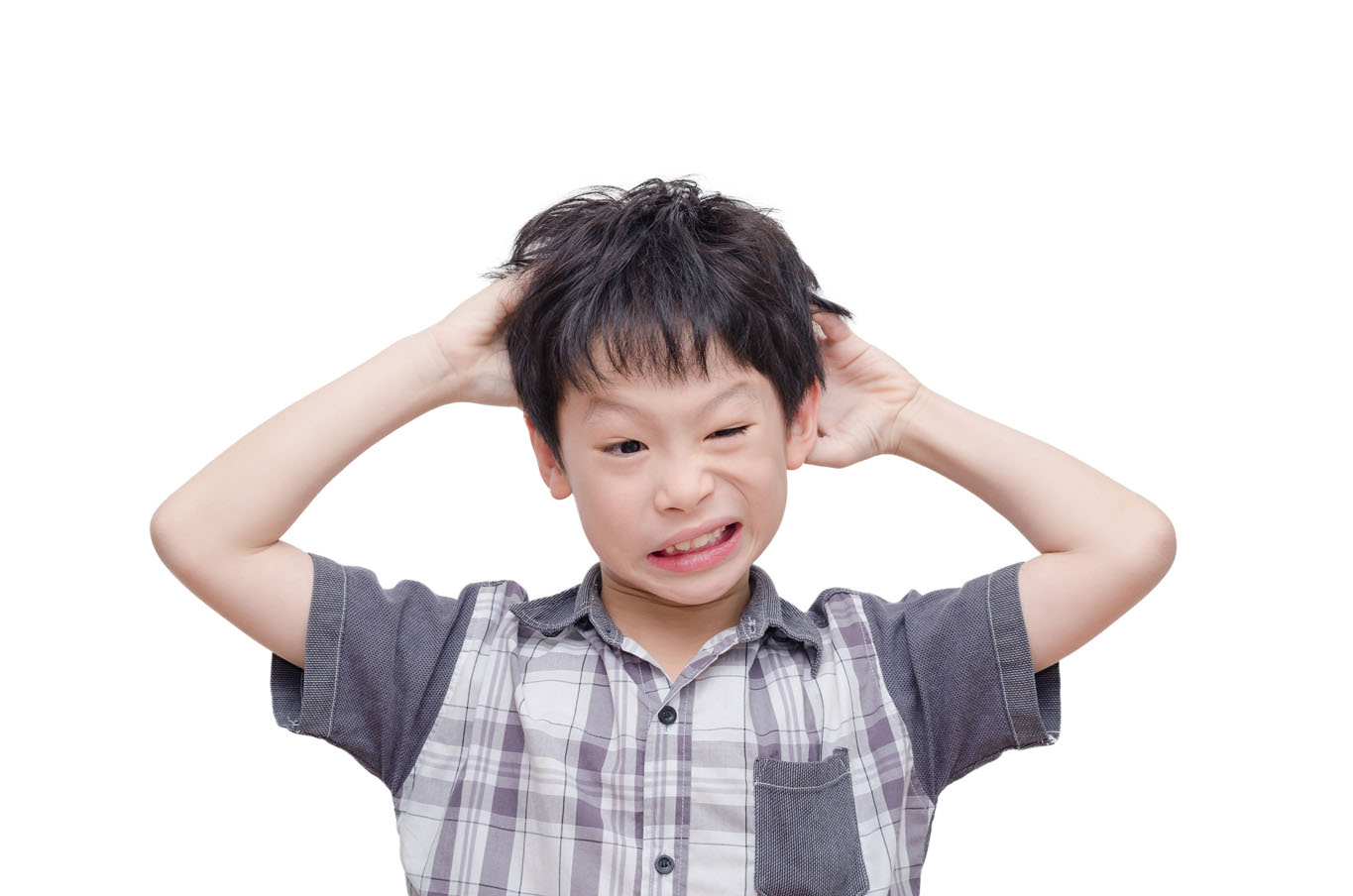 Young boy scratching in his hair and looking uncomfortable