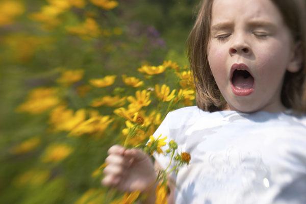 Girl sneezing and holding a bunch of yellow flowers