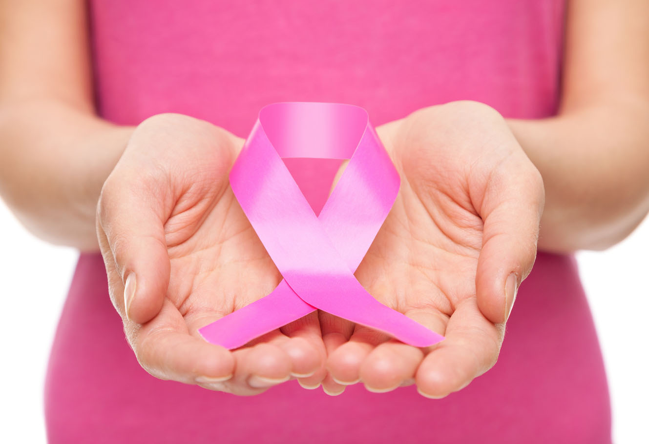 Close up of woman in a pink T-shirt, in her hands she is holding a pink ribbon