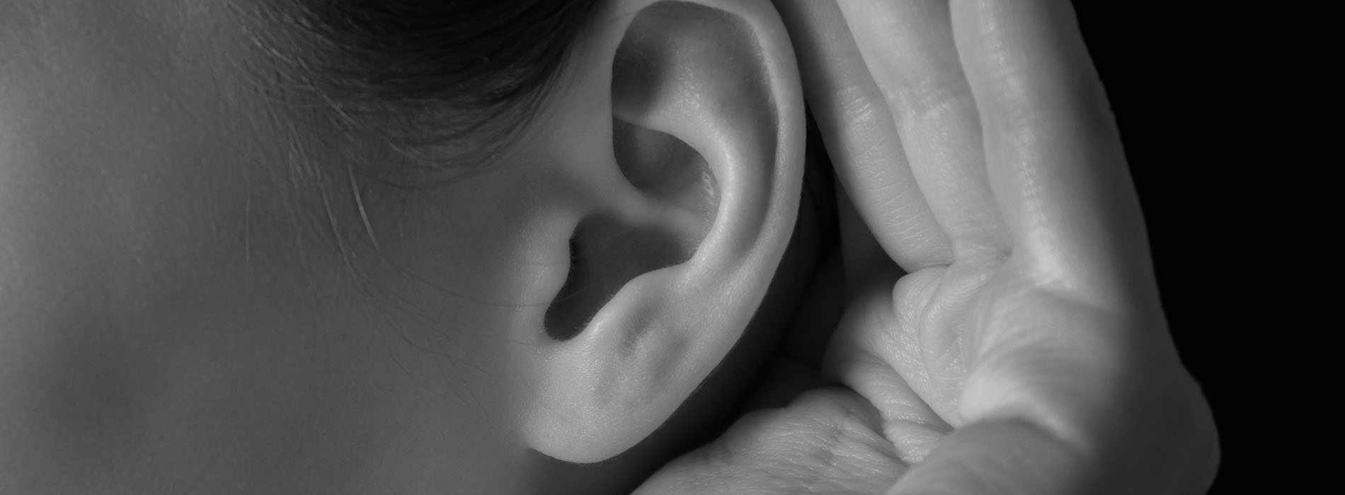 Close up of woman cupping her hand behind her ear