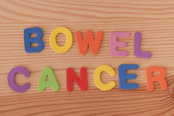 Colour letters spelling out Bowel Cancer against wooden backrgound