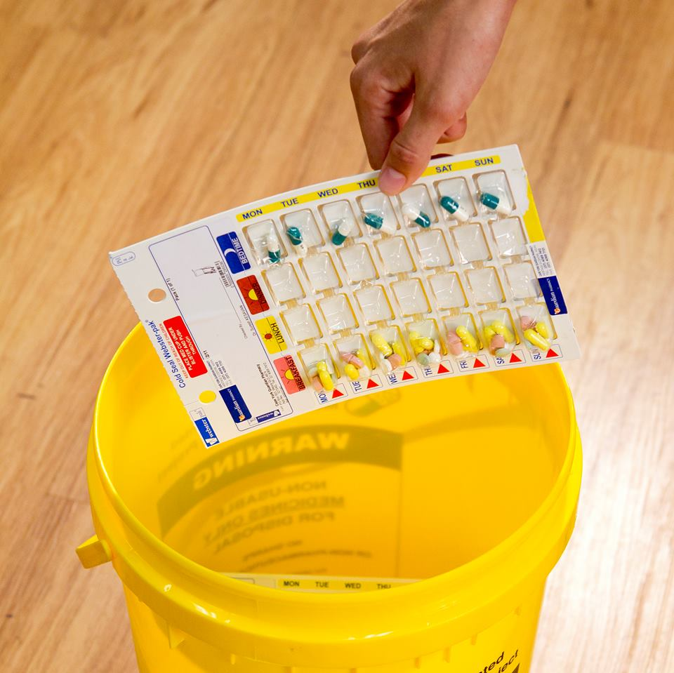 Unwanted medicine being placed in yellow container