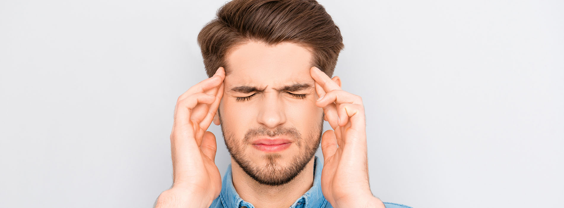 Man hold his hand on either side of his head looking stressed