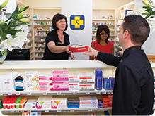 Pharmacist handing a customer their medication at the dispensary counter