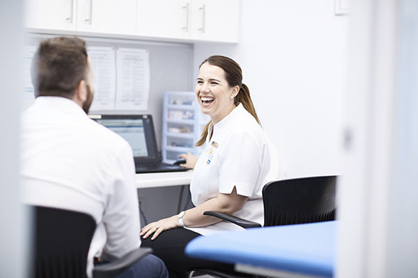 Smiling Pharmacist speaking with a customer